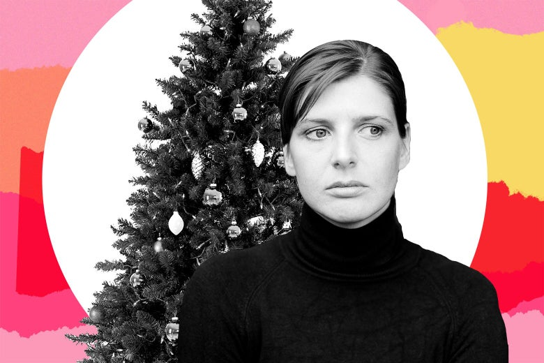 A woman in a black turtleneck has a neutral-to-negative expression in front of a Christmas tree.