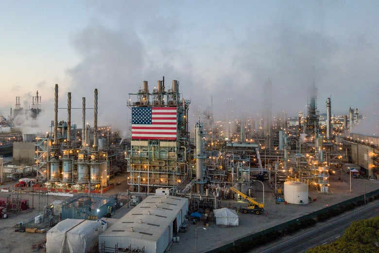 An oil refinery with an American flag is seen spewing smoke.