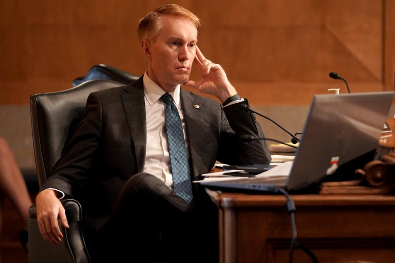 Sen. James Lankford sits with his legs crossed at a table during a committee hearing.