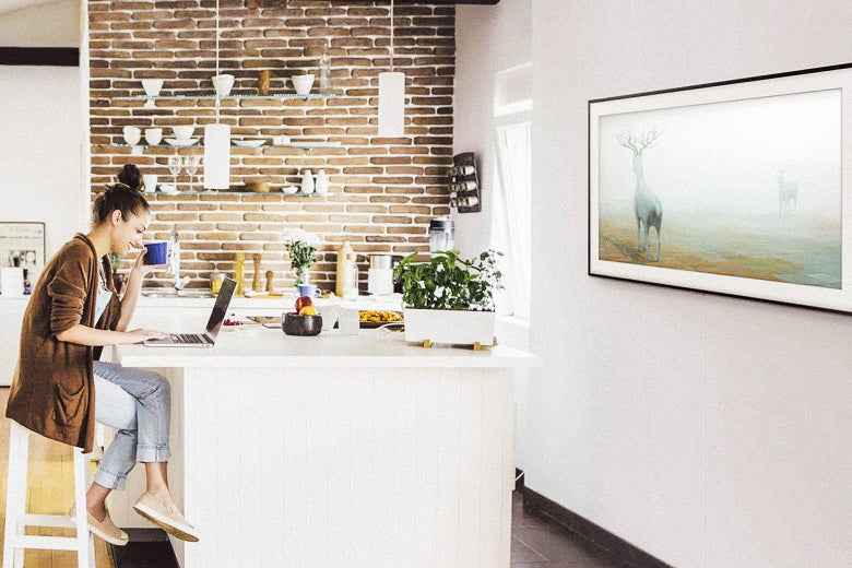 Woman sitting at a kitchen island facing a wall-mounted Samsung Frame TV displaying art.
