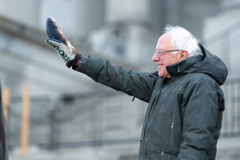Sanders, wearing a coat, waves to a crowd with his right hand, which is clad in a comically large mitten.