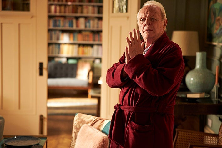 Anthony Hopkins stands wearing a red bathrobe with his hands clasped together.
