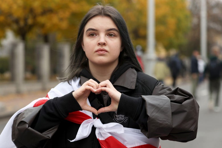 A girl gestures making a heart shape as she takes part in a parade through the streets in Minsk, on October 25, 2020, on the final day of an ultimatum set by the opposition for their embattled strongman leader to resign after months of mass protests. (Photo by Stringer / AFP) (Photo by STRINGER/AFP via Getty Images)