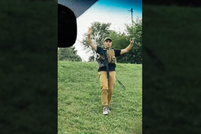 Andreychenko, wearing a tactical vest to which a rifle is attached, holds his hands in the air in a still image from a video.