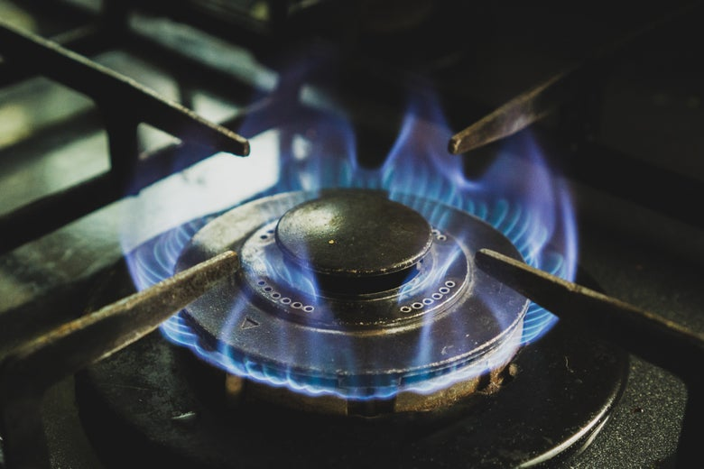 A gas burner lit on a stove.