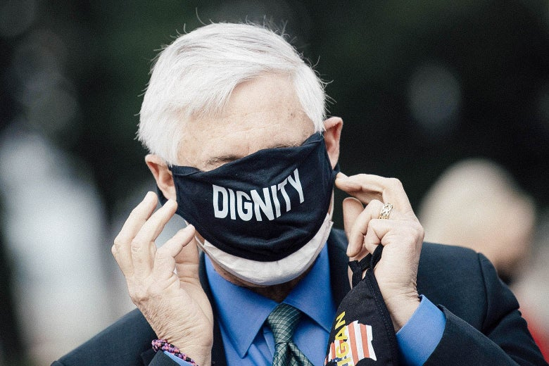 """Rep. Fred Upton puts on a face mask that says """"Dignity"""" across the front. The mask covers his eyes, nose, and mouth."""