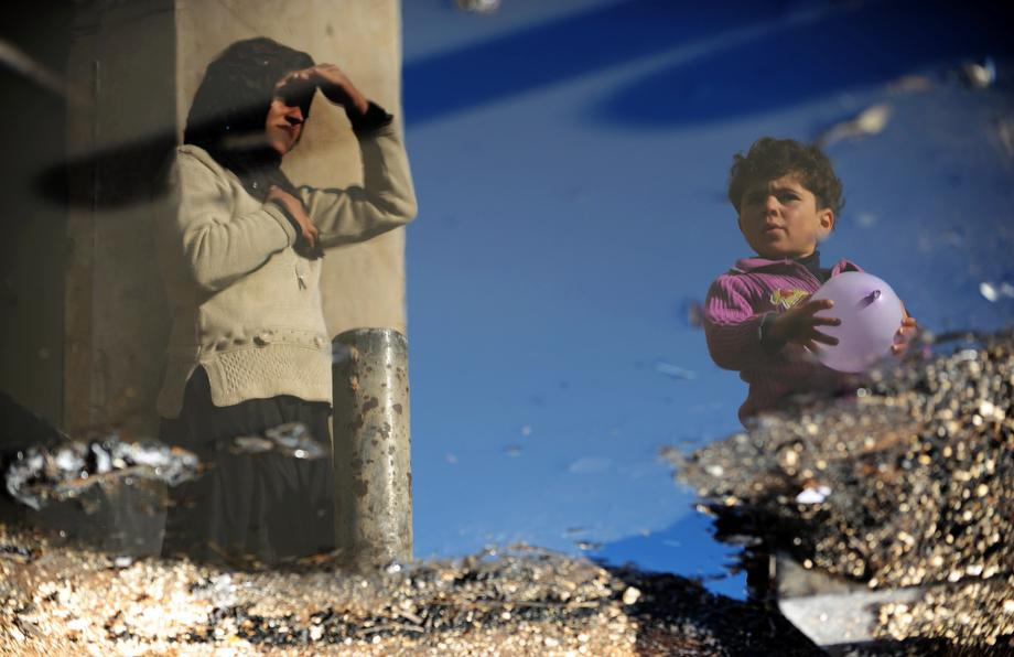A Syrian internally displaced woman and child are reflected in a puddle of water in the Bab al-Hawa camp along the Turkish border in the northwestern Syrian province of Idlib, on March 18, 2013.