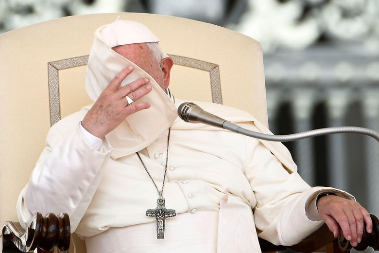 Pope Francis' reaches his hand up as the corner of his cape pellegrina covers his face while he sits in a chair.