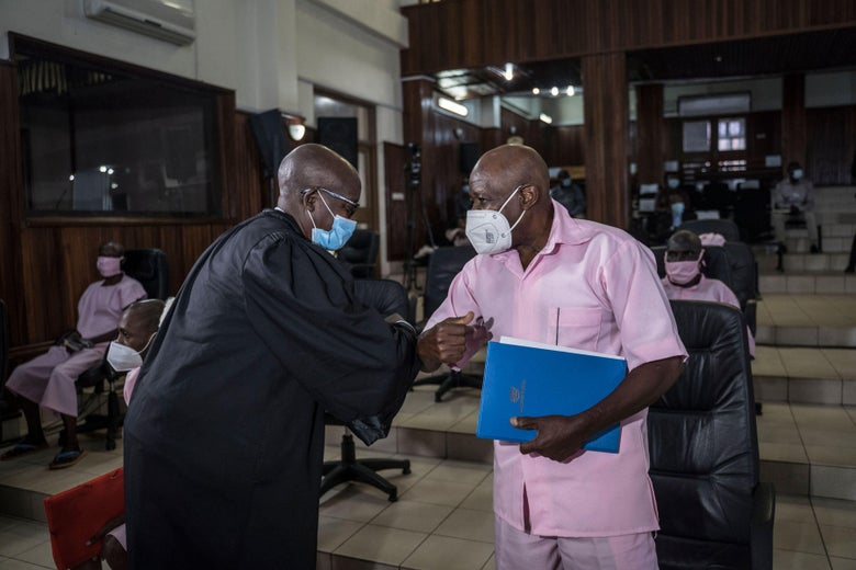 A man in black robes and a mask elbow-bumps with a man in pink clothes and a mask in a courtroom.