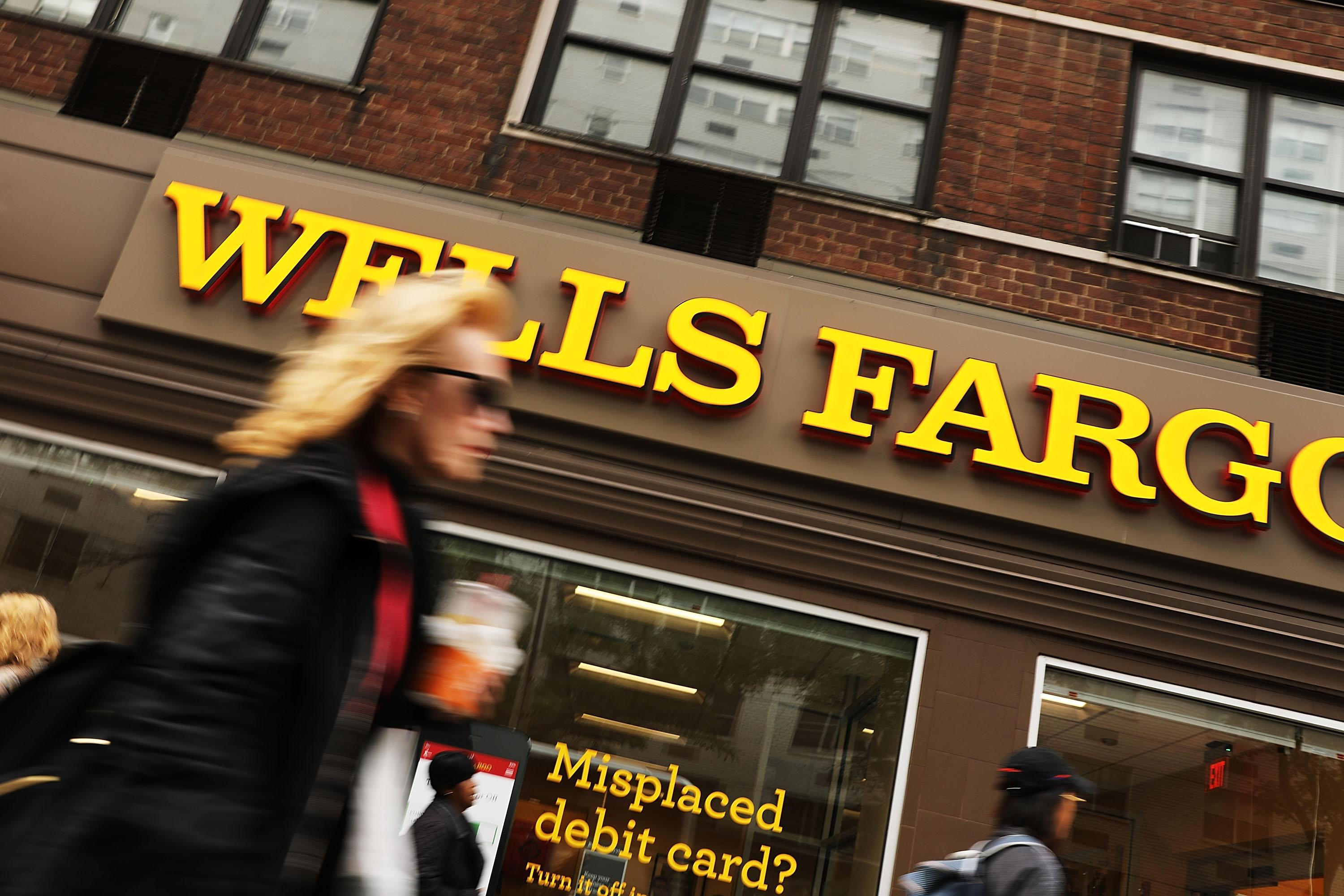 NEW YORK, NY - OCTOBER 13:  People walk by a Wells Fargo bank branch on October 13, 2017 in New York City. Wells Fargo shares were down 3.4% toÊ$53.34Êin afternoonÊtrading following news that the banks quarterly profit from July through September dropped nearly 19%.  (Photo by Spencer Platt/Getty Images)