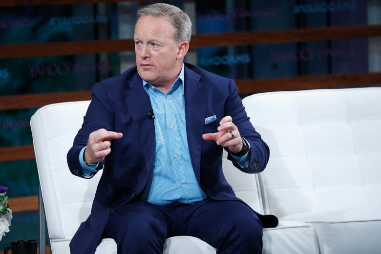 Sean Spicer makes a grasping motion with both hands while seated on a white couch on a stage.