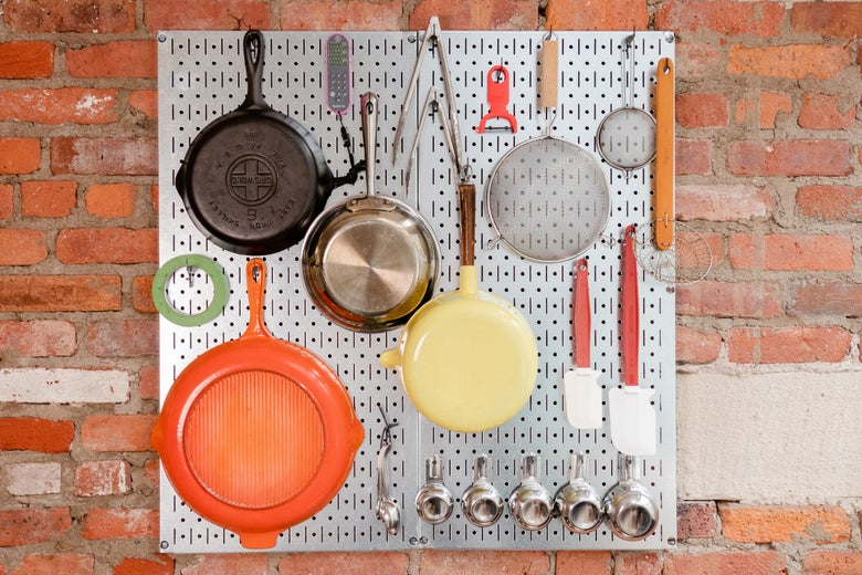 Cookware on a metal pegboard.