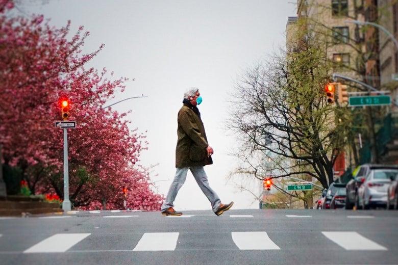 A man walks alone in a crosswalk wearing a mask.