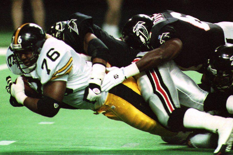 A Pittsburgh player with the ball is tackled by two Atlanta Falcons players.