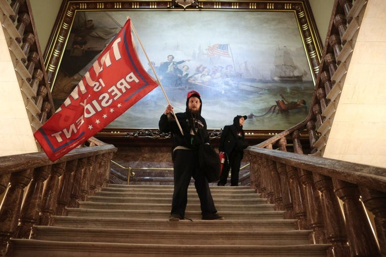 A man carries a large Trump flag up a staircase in front of a large painting.