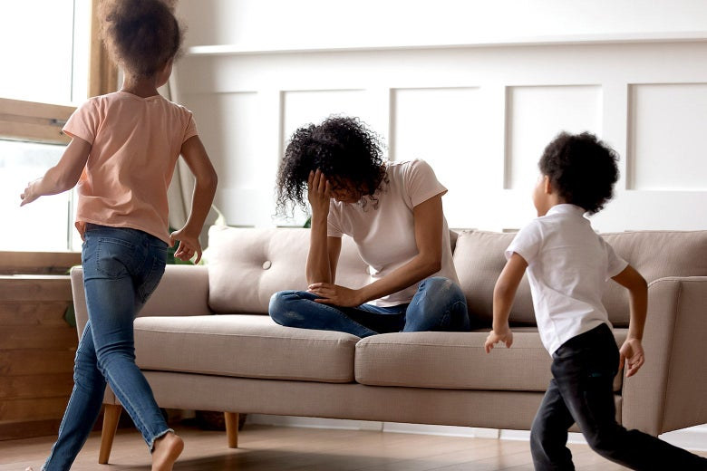 A mom frustrated as her daughter and son run around the living room.