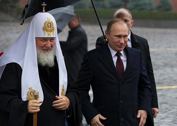 Russian President Vladimir Putin, right, walks with Russian Orthodox Church Patriarch Kirill.