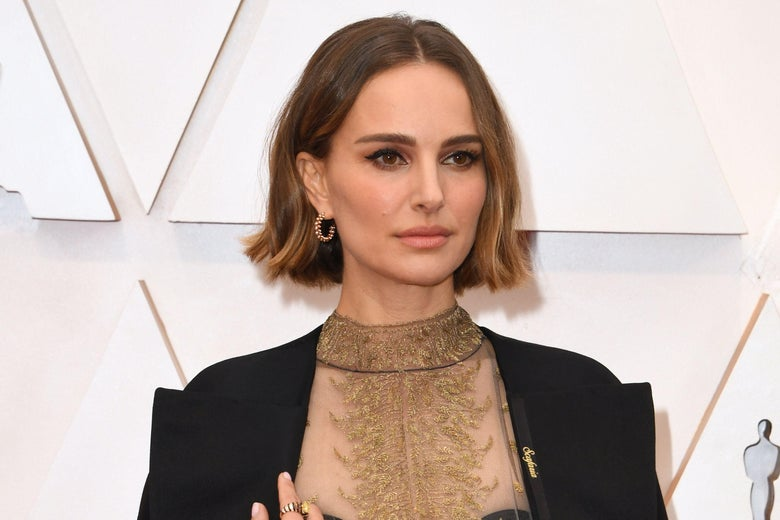 Natalie Portman on the red carpet. She is wearing a black cape with names written on it in gold.