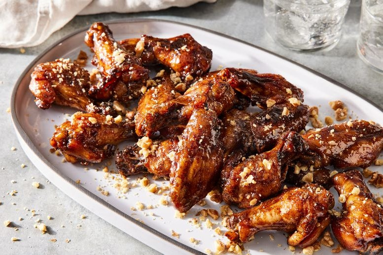 Platter of wings covered in a pomegranate molasses glaze and topped with toasted walnut pieces