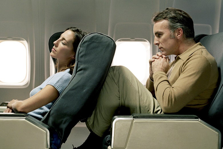 A woman reclining an airplane seat and a man uncomfortable behind her.