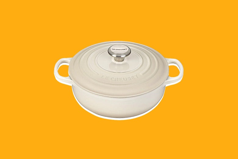 A Le Creuset sauce pot seen against yellow background