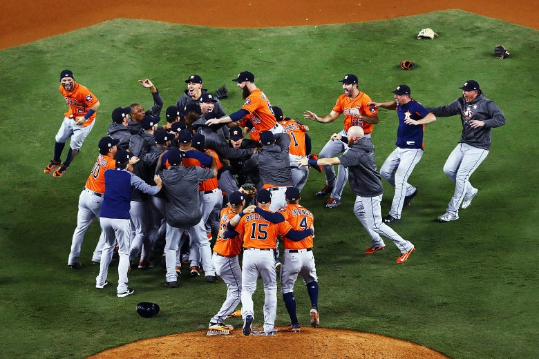 Astros team members rush toward one another near the pitcher's mound.