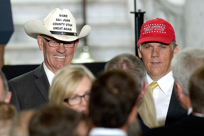 "Bruce Adams wears a ""Make San Juan County Utah Great Again"" cowboy hat and Phil Lyman wears a MAGA hat as they pose for photographs in front of a crowd"