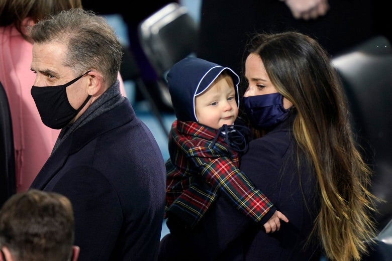 A woman holds a baby wearing a plaid jacket and blue bonnet.
