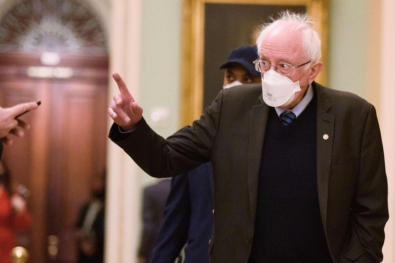 Bernie Sanders raises his index finger while talking to reporters at the Capitol.