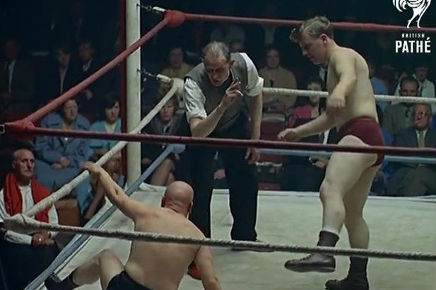 A color still of a wrestling match in the 1960s. In the foreground, one wrestler is getting to his feet as a vicar, refereeing, counts him out. The second wrestler watches from the right.
