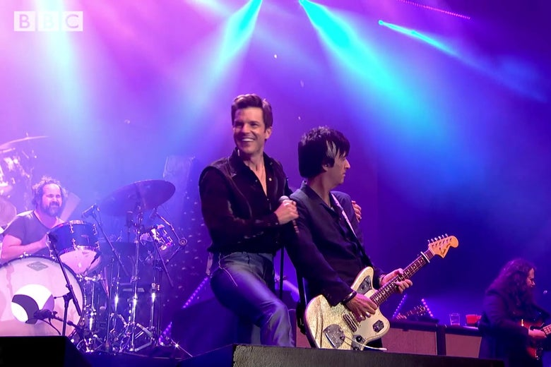 Killers singer Brandon Flowers, on stage at Glastonbury, smiles widely with his arm around Johnny Marr.