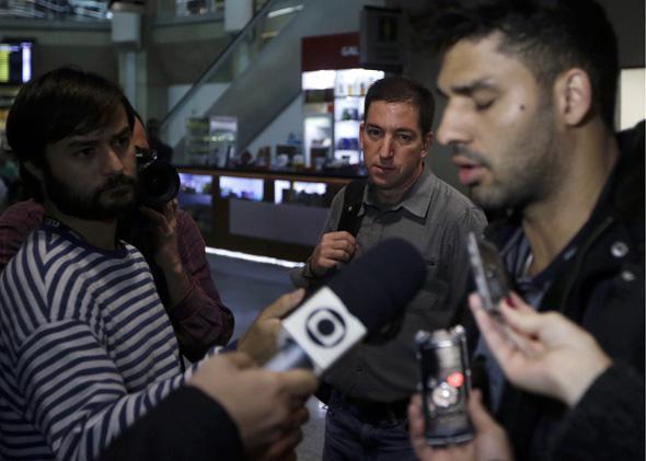 U.S. journalist Glenn Greenwald (C) looks on as his partner David Miranda (R) talks with the media after arriving at Rio de Janeiro.