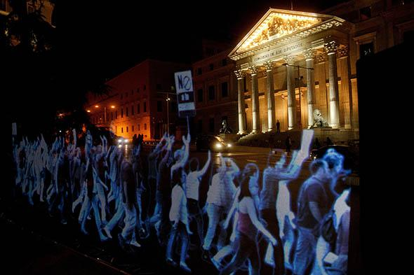Holographic images representing a protest are projected in front