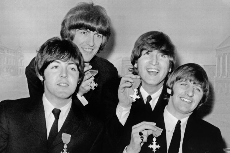 The Beatles showing off their British Empire Medals.