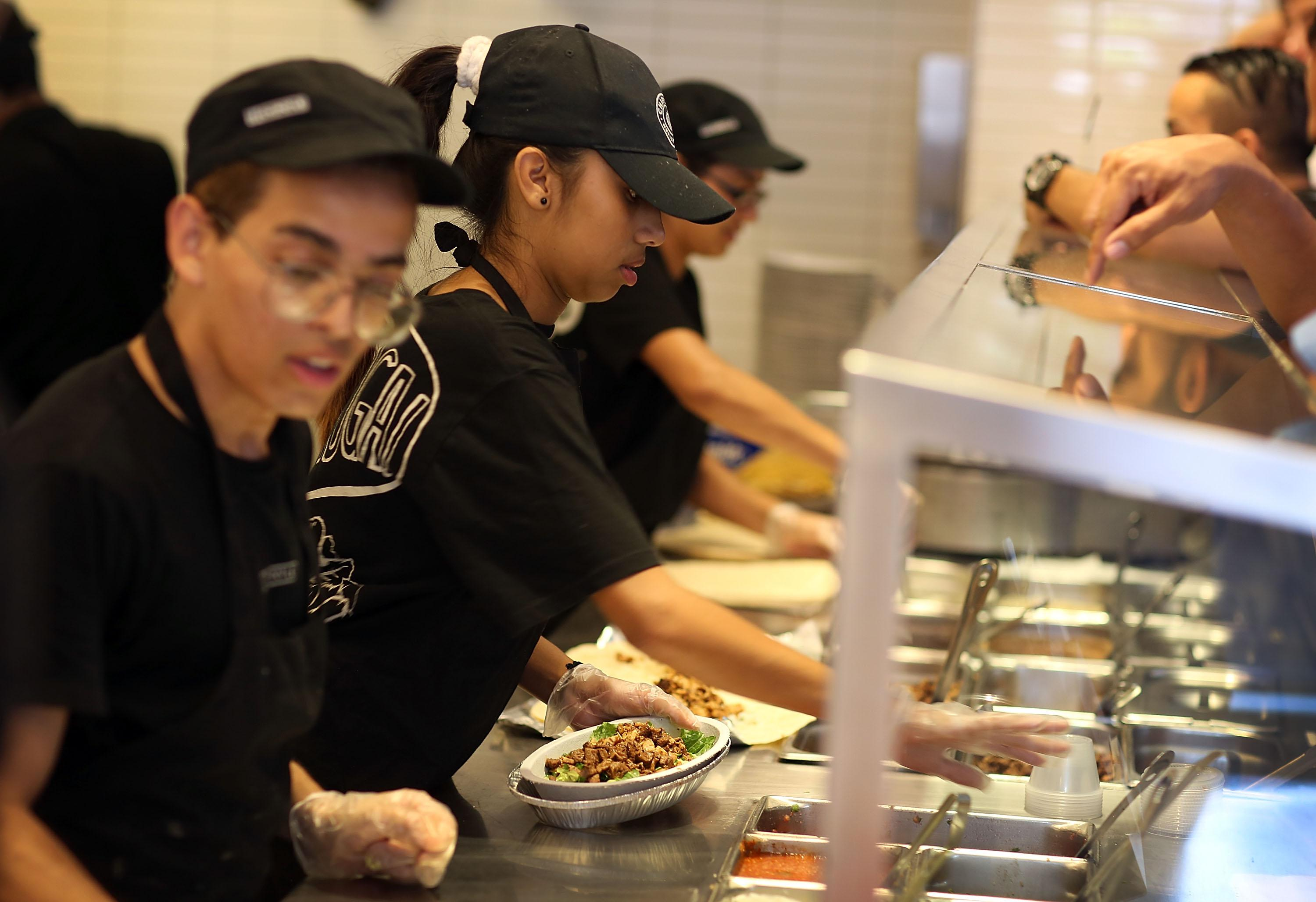 Chipotle restaurant workers fill orders for customers in 2015 in Miami.