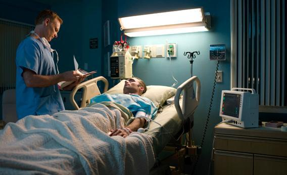 Doctor examining patient in hospital room.
