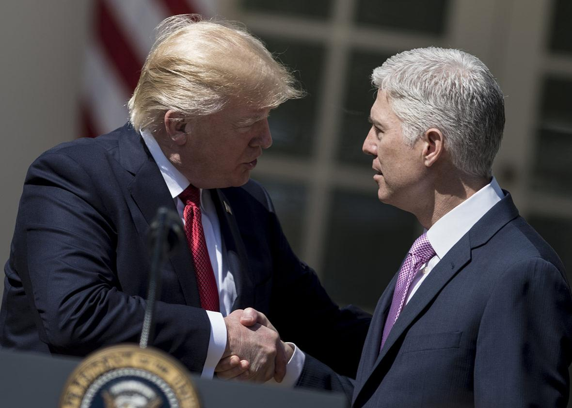Neil Gorsuch (R) shakes US President Donald Trump's