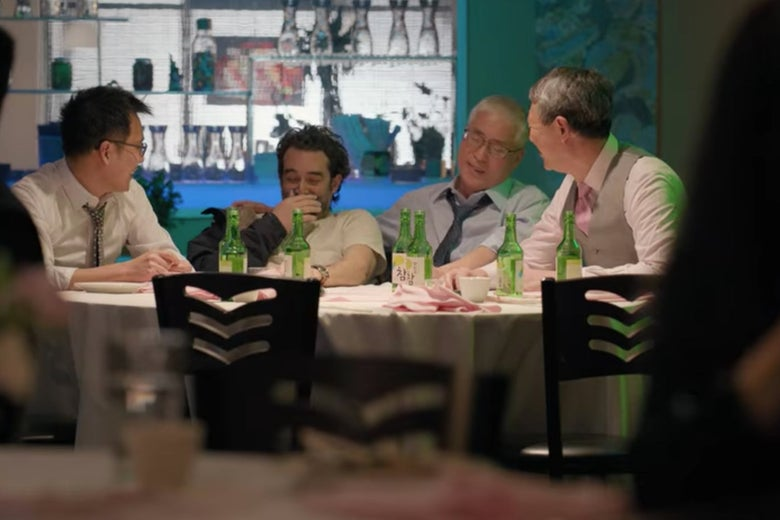 Bill sits with other men at a table at a party.