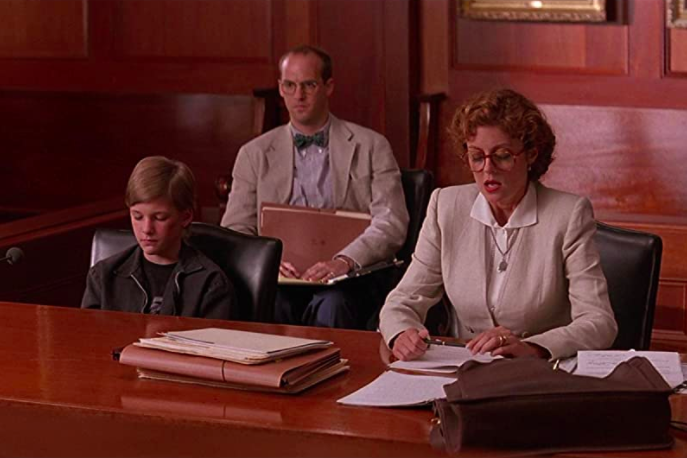 Susan Sarandon and Anthony Edward sit behind a table in a courtroom.