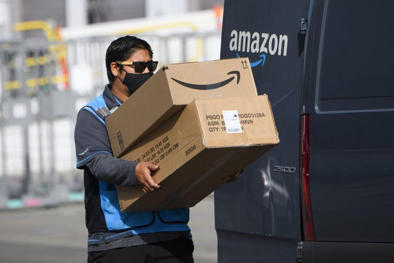An Amazon delivery driver carries boxes into a van outside of a distribution facility on February 2, 2021 in Hawthorne, California.