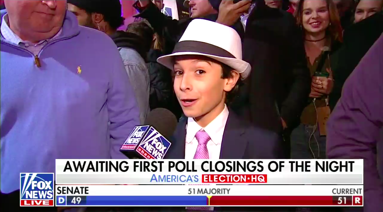 A boy wearing a fedora talks to a Fox News reporter on the street.