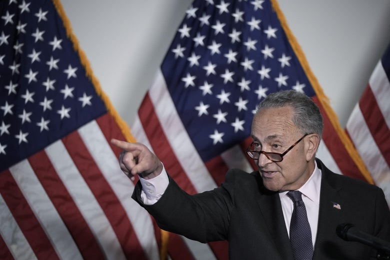 Schumer stands at a podium pointing to a reporter off-screen with three American flags in the background