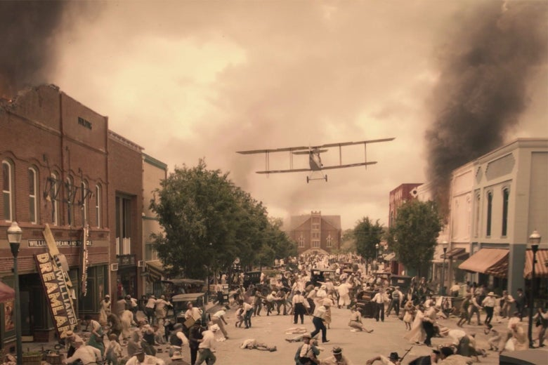 A biplane flies down the main street of Greenwood, above businesses in ruins.