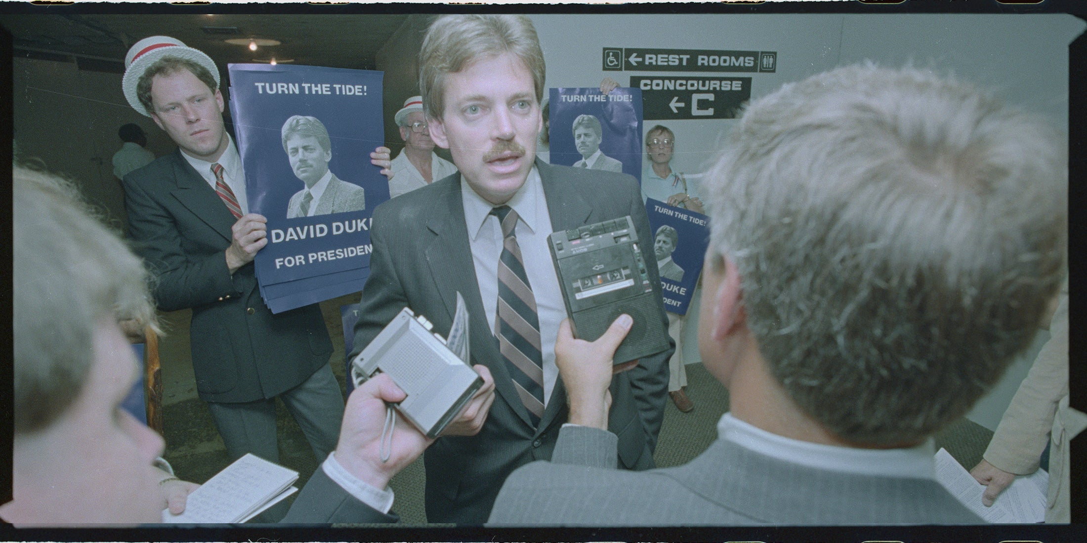 """David Duke surrounded by the press and supporters carrying """"David Duke for President"""" signs"""