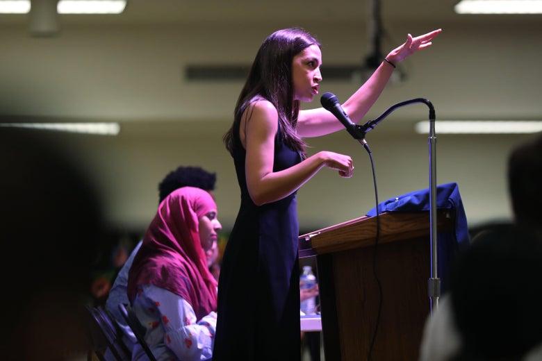 Alexandria Ocasio-Cortez speaking at a podium.