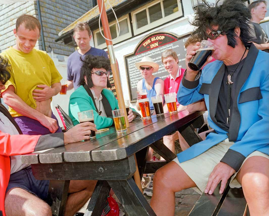 A group of friends in fancy dress drink outside The Sloop Inn pub in St Ives.