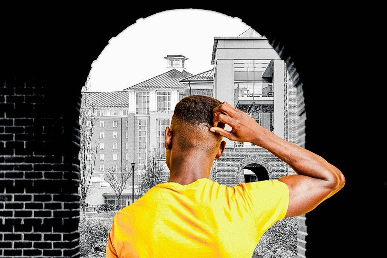 A black man, seen from behind, holds his hand to his head as he looks at campus.