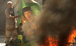 A Libyan rebel burning poster of Qaddafi. Click image to expand.