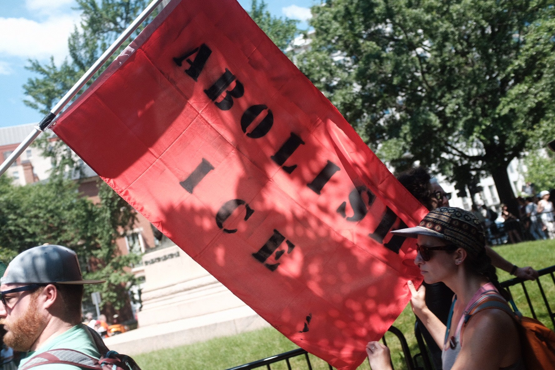 """Two activists carry an """"Abolish ICE"""" banner through Lafayette Park."""