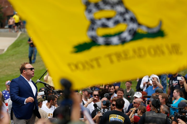"Alex Jones speaks at a public event behind a ""Don't Tread on Me"" flag."